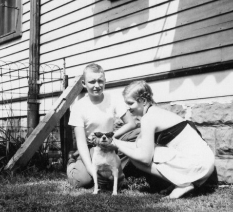 Dad and Aunt Dot dressing up their first dog, a beloved terrier named Spot.