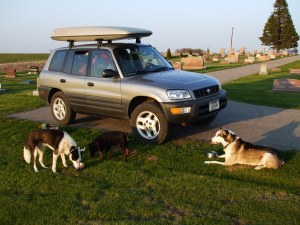 The Toyota Ravioli parked at a cemetery in Texas back when she was just a pup  at only 150,000 miles. Pig, my great Iditarod lead dog, is on the left, Jigs in the center, and Borage to the right.